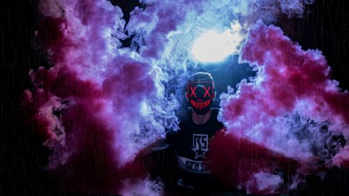 Man wearing a mask through colored smoke HD Wallpaper