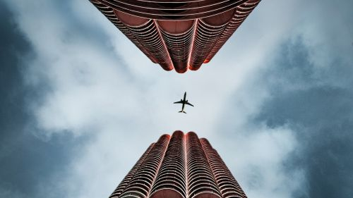 Plane flying over skyscapers HD Wallpaper