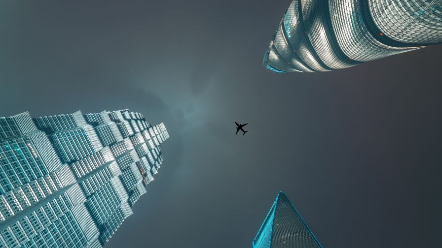 Plane flying over skyscrapers HD Wallpaper