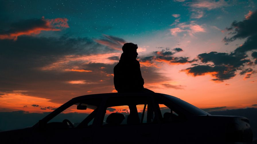 Man standing at the roof of car HD Wallpaper